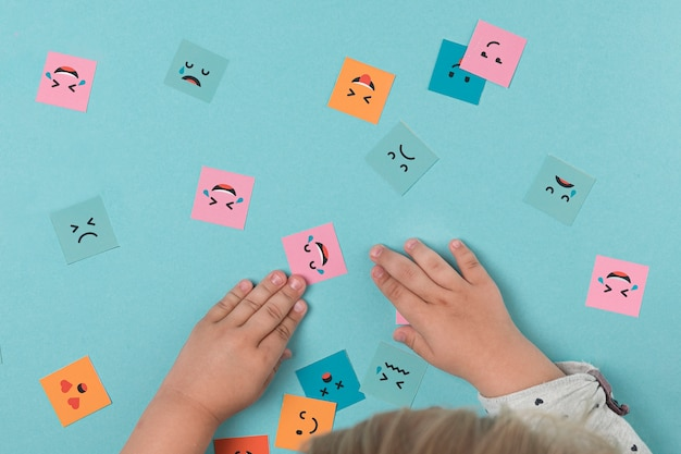 Baby hands playing with smiling faces Free Photo