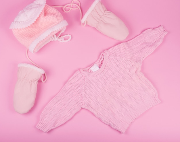 Baby hat, mittens and sweater of pink color Premium Photo