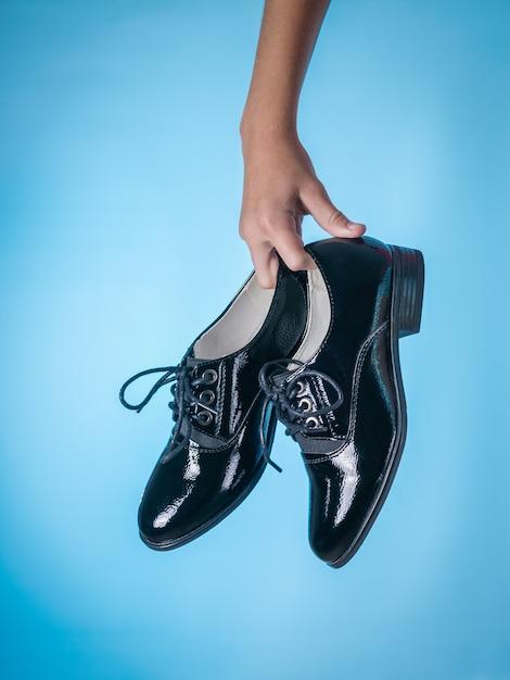 Baby holding fashionable black leather shoes on blue Premium Photo