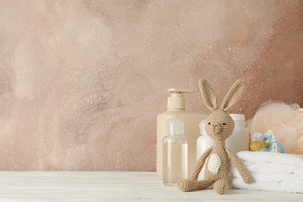Baby hygiene accessories on wooden table against brown wall Premium Photo