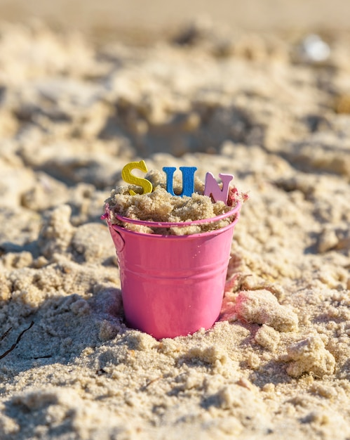 Baby iron bucket filled with wooden colorful letters, inscription sun Premium Photo