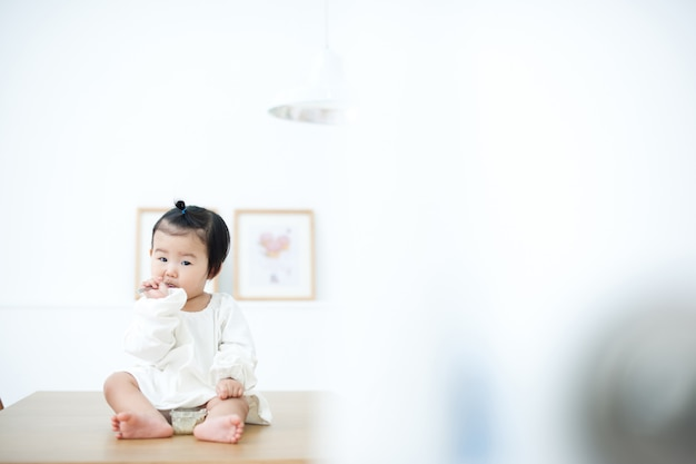 Baby is eating his baby food on a white table. Premium Photo