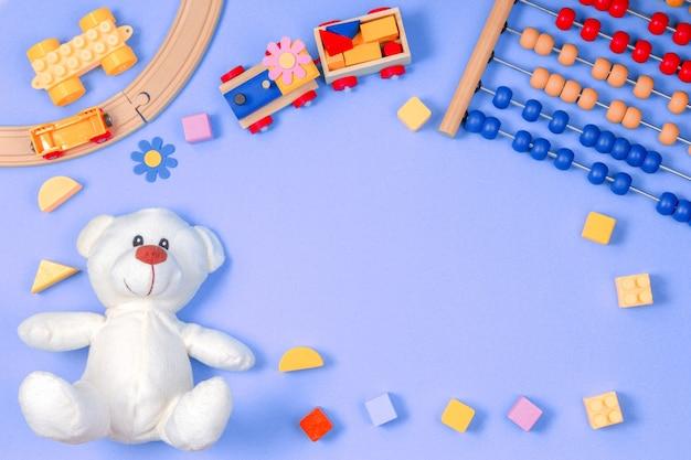 Детские игрушки рамка на синем фоне. вид сверху. плоская планировка. скопируйте место для текста Premium Фотографии