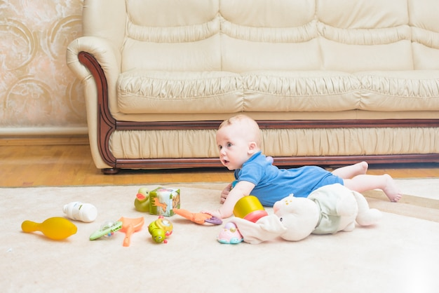 Baby laying with many toys on carpet at home Free Photo