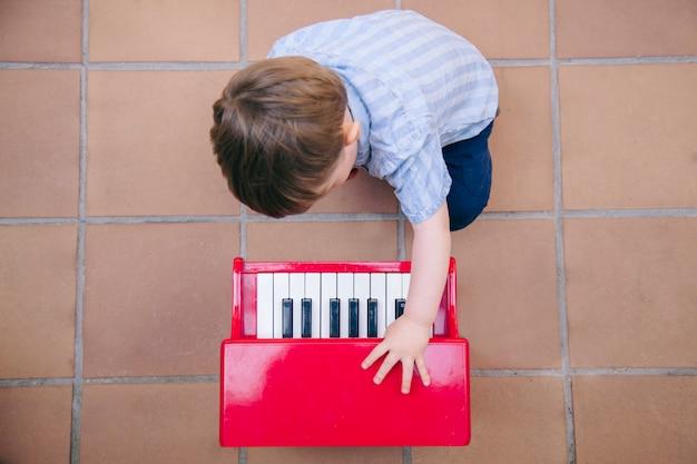 Ребенок учится играть музыку дома с фортепиано для детей. Premium Фотографии
