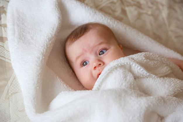 赤ちゃん、寝室のベッドの上、タオル、ラップ、笑顔 Premium写真