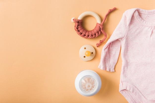 おもちゃ;おしゃぶり;オレンジ色の背景の上にミルクボトルとピンクのbaby onesies 無料写真