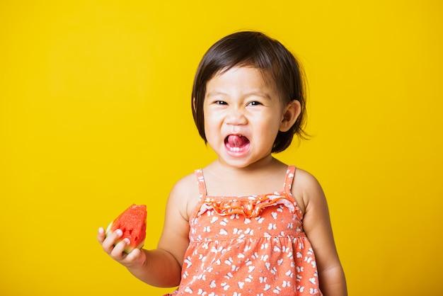 赤ちゃんや子供かわいい女の子魅力的な笑い笑顔tシャツを着て遊んで保持するスイカを食べて新鮮です Premium写真