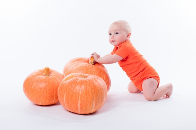 Baby in orange tshirt on white tshirt sits next to pumpki Premium Photo