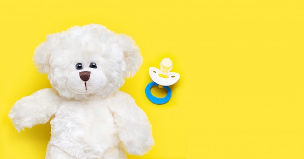 Baby pacifier with toy white bear on yellow. Premium Photo