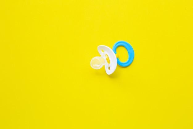 Baby pacifier on yellow Premium Photo