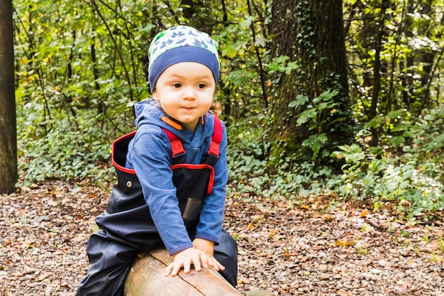 Baby playing on a forest path in autumn Premium Photo