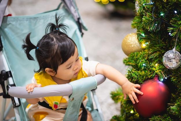 Baby playing with christmas ball and pine tree Premium Photo