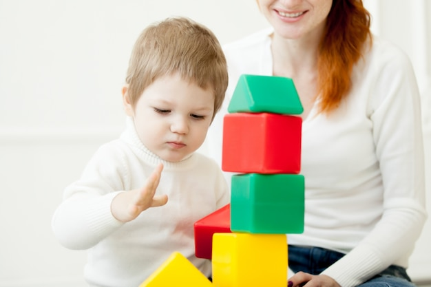Baby playing with colorful toy blocks Free Photo