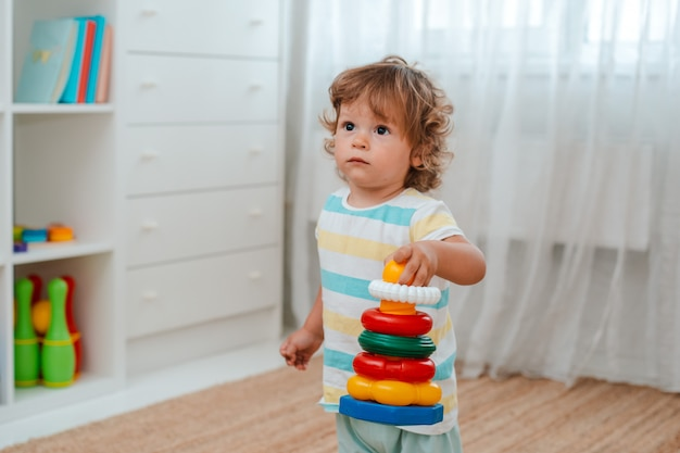 Baby plays on the floor in the room in educational plastic toys Premium Photo