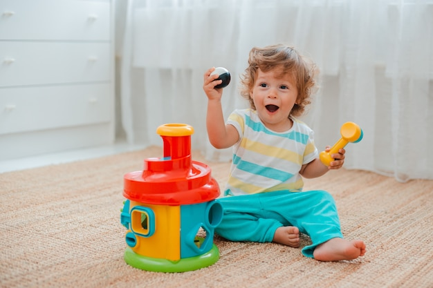 Baby plays on the floor in the room in educational plastic toys. Premium Photo