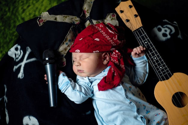 Baby in a rocker bandana lies with a guitar and a microphone Premium Photo