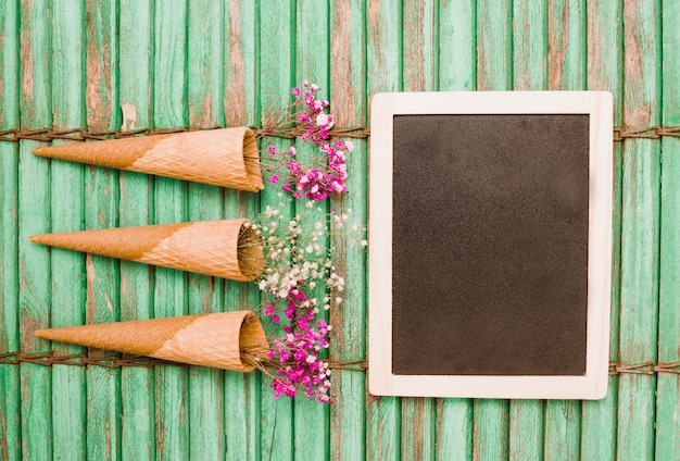 Baby's-breath flowers in cone with wooden blank slate on green wooden shutter backdrop Free Photo