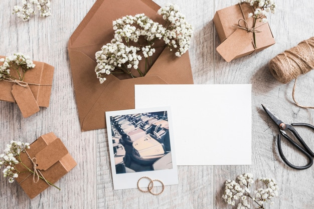Baby's-breath flowers in the envelope with blank paper; wedding rings; spool and polaroid frame Free Photo