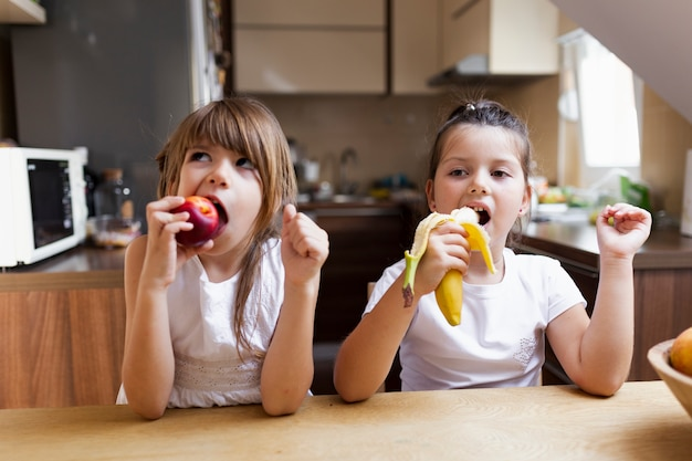 Baby sisters having a healthy snack Free Photo