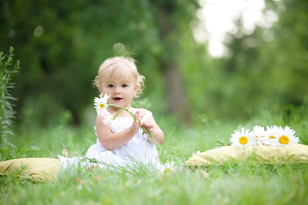 Baby sitting on green grass Premium Photo