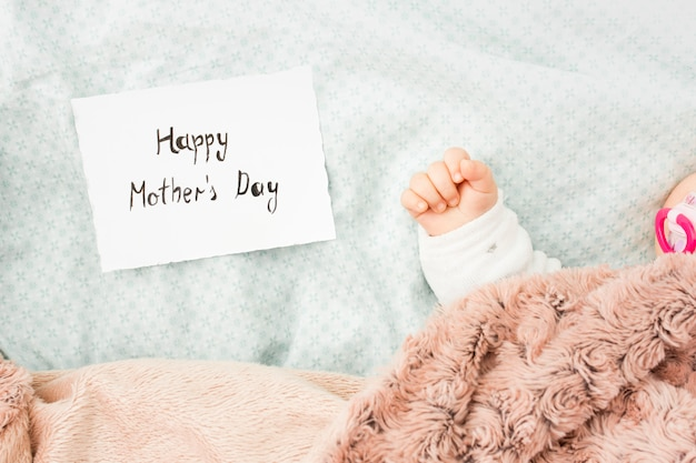 Baby sleeping in bed near happy mothers day inscription Free Photo