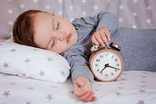 Baby sleeping in a crib with an alarm clock Premium Photo