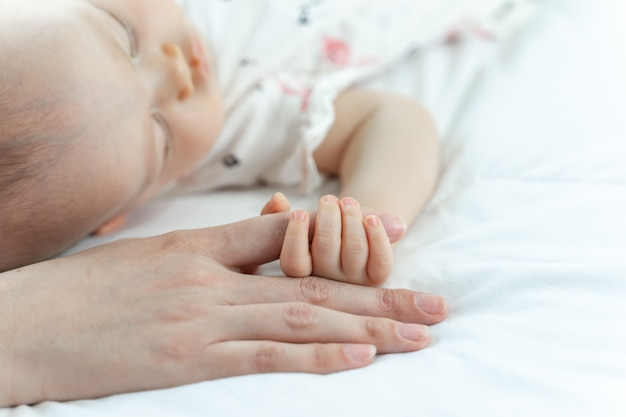 Baby sleeping and grabbing her mother's finger Free Photo