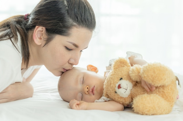 Baby sleeping with a teddy bear and mother kissing her Free Photo