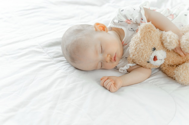 Baby sleeping with a teddy bear Free Photo