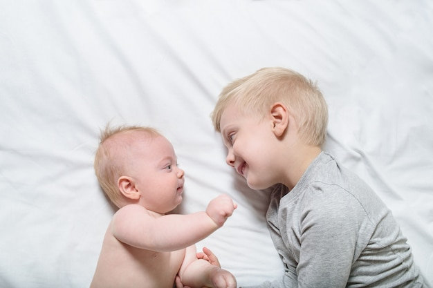 Baby and smiling older brother are lying on the bed. they play, communicate and interact. top view Premium Photo