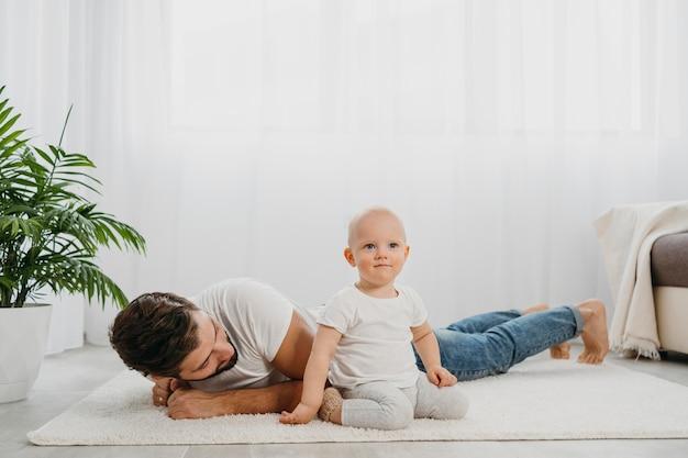 Bambino in piedi sul pavimento a casa con il padre Foto Gratuite