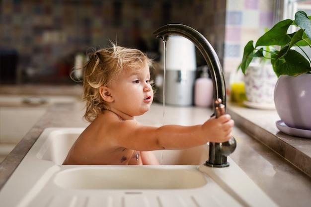 Baby taking bath in kitchen sink. Premium Photo