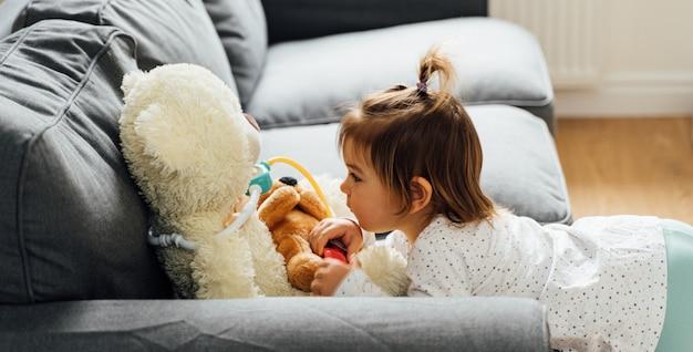 医師のキットと人形のおもちゃで遊ぶ幼児の女の子 Premium写真