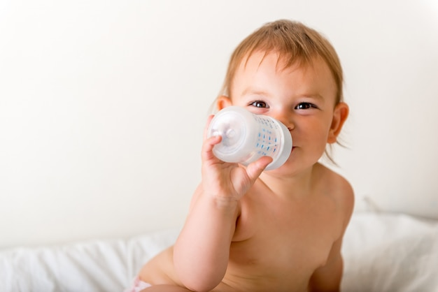 Baby toddler sits on the white bed, smiles and drinks water from plastic bottle Premium Photo