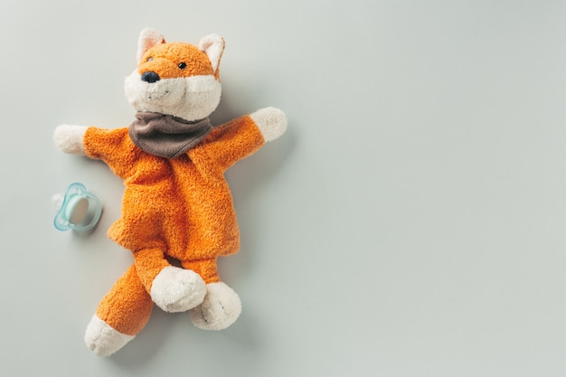 Baby toy red fox and nipple on pastel Premium Photo