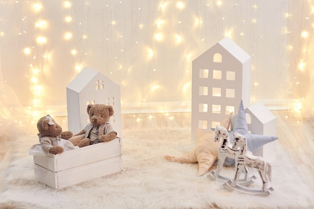 Baby toys and toy house on a background of christmas lights. holiday decor Premium Photo