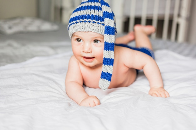 Baby wearing striped knitted hat Free Photo