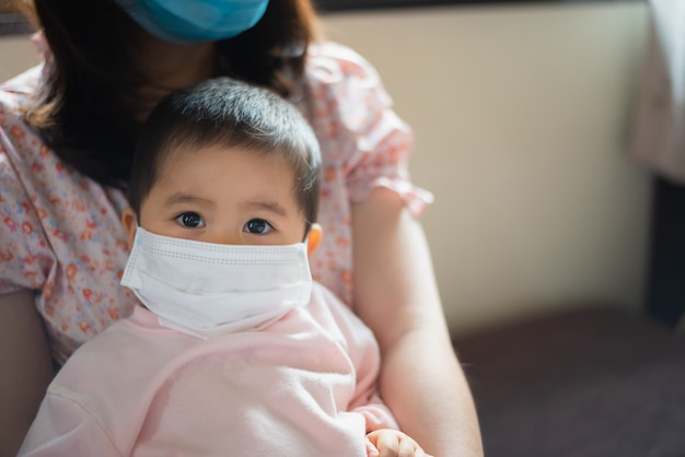 Premium Photo | Baby wearing surgical mask stay at home.