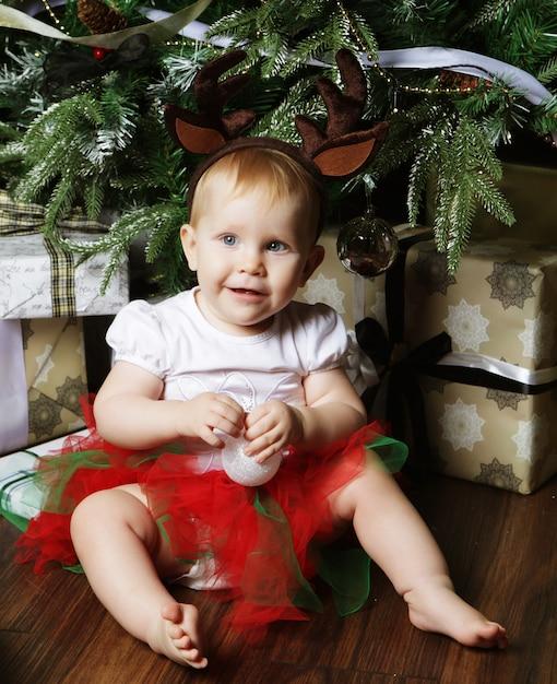 Ребенок с елкой и подарками Premium Фотографии