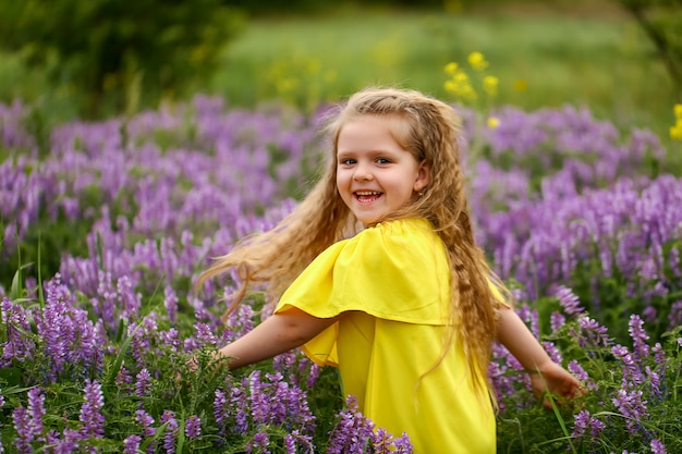 Baby with curls spinning in a field of lavender, dressed in a yellow sundress, summer evening Premium Photo
