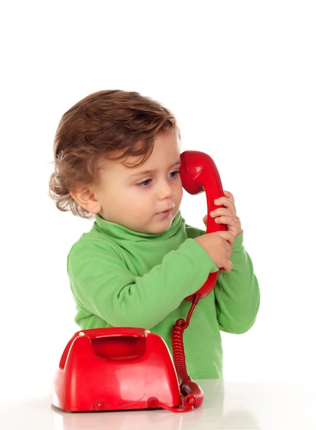 Baby with one years old playing with a red phone Premium Photo