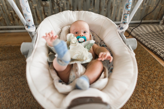 Baby with pacifier lying on baby carriage at home Free Photo