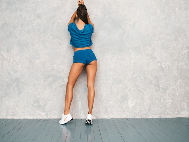 Back of fitness woman in sports clothing looking confident.young female wearing sportswear. beautiful model with perfect tanned body.female posing in studio near gray wall Free Photo