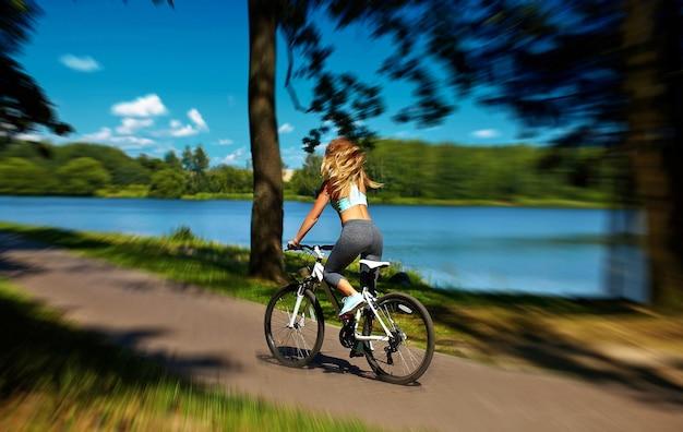空気中の高い髪を飛んで湖の近くの緑の夏の公園で自転車に乗ってセクシーなホットスポーツブロンド女性少女モデルの裏 無料写真