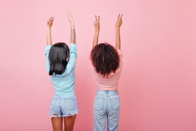 ジーンズでブルネットの女の子をストレッチの後ろ。手を上げてポーズをとる古着の華やかな黒髪の女性。 無料写真