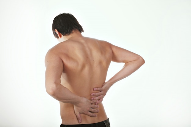Back pain: a man on a white background holding his sore torso Premium Photo