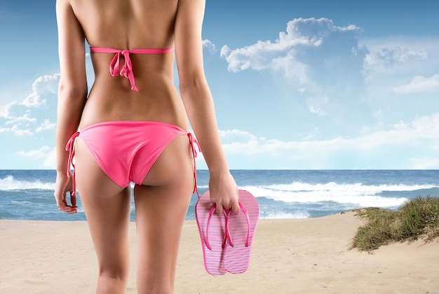 Back portrait of beautiful woman with flip flops on a beach Free Photo