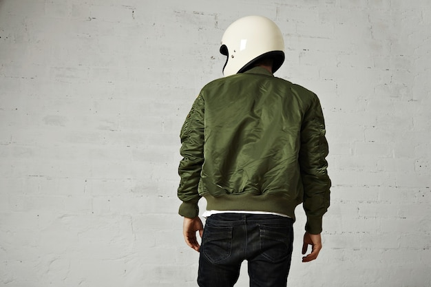 Back portrait of a motorcyclist in white helmet and green bomber jacket isolated on white Free Photo