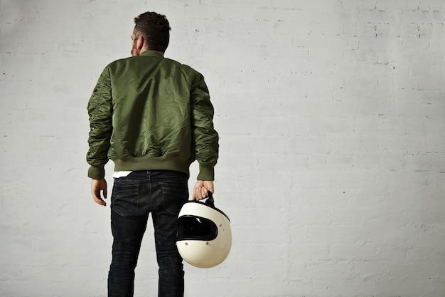 緑のボンバージャケット、スキニージーンズ、白い壁と彼の手に白い空白のヘルメットでヒップひげを生やしたパイロットの背中の肖像画 無料写真